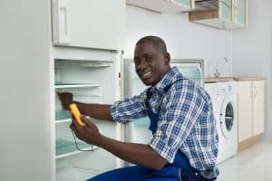 Happy African Technician Repairing Refrigerator Appliance In Kitchen Room